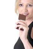Mujer alrededor para comer una barra de chocolate Imagenes de archivo