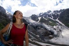 Mujer alta en las montañas, nieve, vidrieros, nubes Foto de archivo