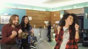 Mujer alta-fiving a sus amigos después de lanzar una bola de bolos almacen de video