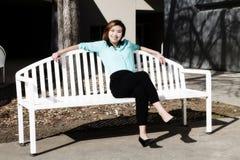 Mujer americana asiática joven sonriente que se sienta en banco Imágenes de archivo libres de regalías