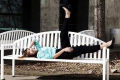 Mujer americana asiática sonriente que descansa en banco al aire libre Fotos de archivo