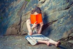 Mujer americana joven que lee el libro rojo, sentándose en la tierra, thinki Fotos de archivo libres de regalías