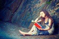 Mujer americana joven que lee el libro rojo, sentándose en la tierra, viajando en Nueva York en verano Fotos de archivo