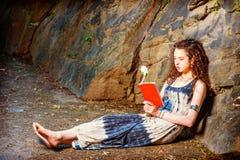 Mujer americana joven que lee el libro rojo, sentándose en la tierra, viaje Imágenes de archivo libres de regalías