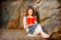 Mujer americana joven que lee el libro rojo, sentándose en la tierra, viaje Fotos de archivo