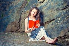 Mujer americana joven que lee el libro rojo, sentándose en la tierra, viaje Imagen de archivo libre de regalías