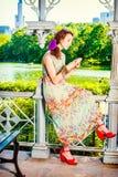 Mujer americana joven que manda un SMS en el teléfono celular, el viajar, relajándose Imagen de archivo