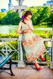 Mujer americana joven que manda un SMS en el teléfono celular, el viajar, relajándose Fotografía de archivo