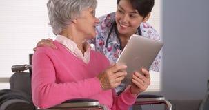 Mujer amistosa y paciente mayor que hablan con la tableta Imágenes de archivo libres de regalías