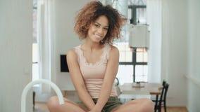 Mujer amxerican afro joven feliz que se sienta en una tabla de cocina en casa almacen de video