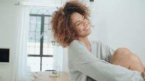 Mujer amxerican afro joven feliz que se sienta en una tabla de cocina en casa metrajes