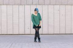 Mujer andrógina adolescente que mira abajo con el pelo teñido azul aislado Foto de archivo libre de regalías