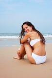 Mujer animada que se sienta en la arena Foto de archivo libre de regalías