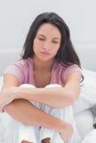 Mujer ansiosa sentada en su cama Imágenes de archivo libres de regalías