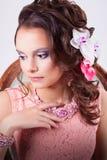 Mujer apacible en un vestido rosado y un collar rosado pensativos Fotos de archivo libres de regalías