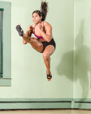 Mujer apta alto Mid Air de retroceso con el pie Fotografía de archivo libre de regalías