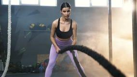 Mujer apta atractiva durante el entrenamiento con las cuerdas de la batalla en el gimnasio almacen de video