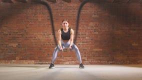 Mujer apta caucásica que ejercita con las cuerdas de la batalla en el gimnasio metrajes