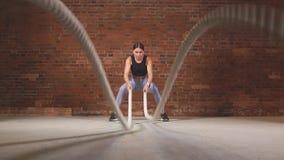 Mujer apta caucásica que ejercita con las cuerdas de la batalla en el gimnasio Cámara lenta almacen de video