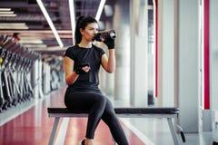 Mujer apta con la botella usando su teléfono elegante con los auriculares en gimnasio Imágenes de archivo libres de regalías