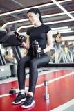 Mujer apta con la botella usando su teléfono elegante con los auriculares en gimnasio Foto de archivo