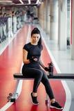 Mujer apta con la botella usando su teléfono elegante con los auriculares en gimnasio Fotos de archivo libres de regalías