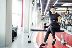 Mujer apta con la botella usando su teléfono elegante con los auriculares en gimnasio Fotos de archivo