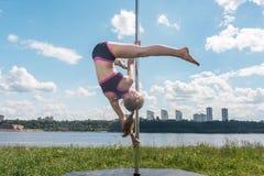 Mujer apta de la danza de poste que ejercita con el pilón al aire libre Fotografía de archivo