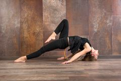 Mujer apta de los jóvenes que hace actitud de la yoga del matsyasana Foto de archivo libre de regalías