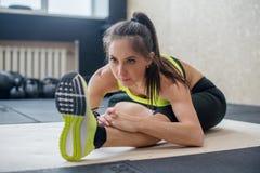 Mujer apta de los jóvenes que hace el ejercicio delantero asentado del doblez, el estirar femenino deportivo imagen de archivo libre de regalías