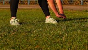 Mujer apta de los jóvenes que hace estirando ejercicios en parque almacen de video