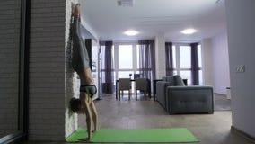 Mujer apta de los jóvenes que hace posición del pino cerca de la pared en casa almacen de video