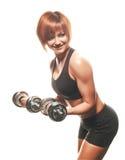 Mujer apta de los jóvenes que hace rizos de la pesa de gimnasia Imagen de archivo