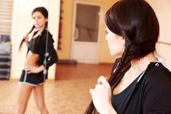 Mujer apta de los jóvenes que mira su reflexión en espejo Fotos de archivo