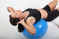 Mujer apta de los jóvenes que usa la bola del ejercicio para el entrenamiento Foto de archivo libre de regalías