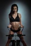 Mujer apta del gimnasio atractivo que se coloca en el aparato de remar Fotografía de archivo