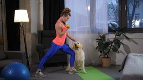 Mujer apta deportiva con los brazos auxiliares del entrenamiento del perro almacen de metraje de vídeo