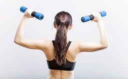 Mujer apta durante el ejercicio con pesas de gimnasia, visión trasera Imagen de archivo