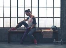 Mujer apta en el engranaje del entrenamiento que se sienta en banco en gimnasio del desván Fotografía de archivo