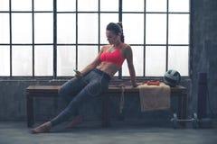 Mujer apta en el gimnasio del desván que se sienta en el banco que selecciona música Foto de archivo