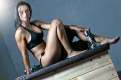 Mujer apta en el gimnasio que se sienta en las cajas del plyo Foto de archivo libre de regalías