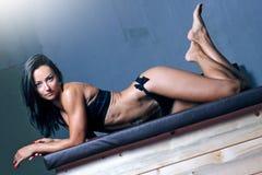 Mujer apta en el gimnasio que se sienta en las cajas del plyo Foto de archivo