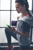Mujer apta en engranaje del ejercicio en el gimnasio del desván que mira abajo el teléfono Imagen de archivo libre de regalías
