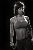 Mujer apta en un fondo negro con pesas de gimnasia Fotos de archivo libres de regalías