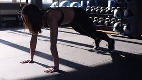 Mujer apta joven atractiva que lleva un sujetador negro y las polainas de los deportes que hacen ejercicios en el piso en un gimn metrajes