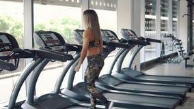 Mujer apta joven que hace ejercicio de funcionamiento en gimnasio almacen de metraje de vídeo