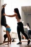 Mujer apta joven que hace ejercicio de la posici?n del pino en gimnasio fotografía de archivo libre de regalías
