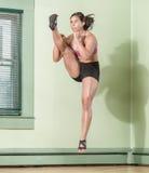Mujer apta Mid Air de retroceso con el pie Imagenes de archivo