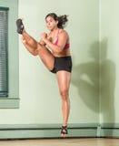 Mujer apta Mid Air de retroceso con el pie en ángulo Imagen de archivo libre de regalías