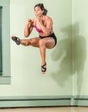 Mujer apta Mid Air recto de retroceso con el pie Fotos de archivo